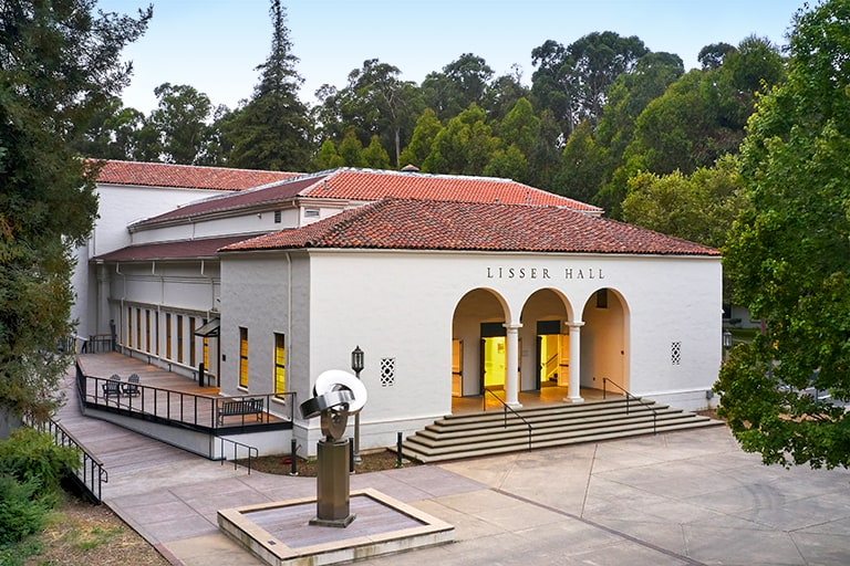 A sweeping view historic Lisser Hall shows the mission-style building and its side terrace surrounded by trees on the Mills College campus.