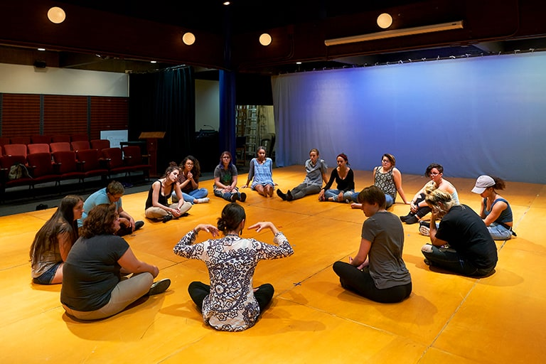 A group of performing artists are seated in a circle on the stage of Mills College's Rothwell Theater, which is available for community rentals.