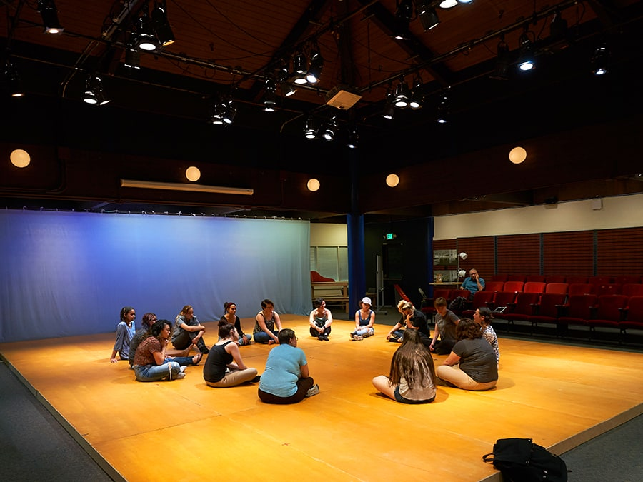 Students sit in a circle on the sprung flooring of the intimate Rothwell Theater on the Mills College campus.