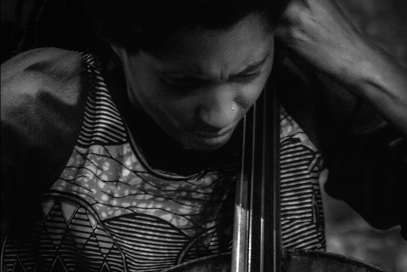 Tomeka Reid's eye's are closed, head leaning forward. Their cheek hovers near the neck of the cello. Left hand is raised playing. Black and White. Photo by Scott Hesse.