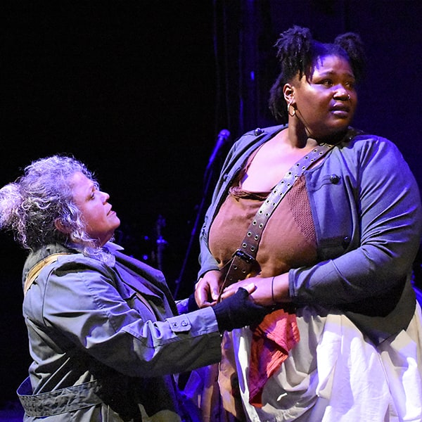 Actresses with the Oakland-based Ubuntu Theater Project clutch hands during a performance on stage on the Mills College campus.
