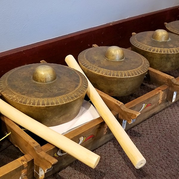 A display of knobbed brass gongs called gamelan. This traditional Indonesian instrument is featured in works by Mills College alumnus Brian Baumbusch.