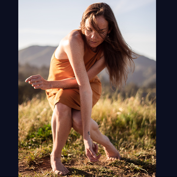 Casey Thorne dances outside, feet on bare ground, surrounded by tall grasses and a mountain on the horizon. Dressed in an orange dress, their left knee locks in behind a deeply bent right leg, with their right arm draped long over the left, reaching for the ground.