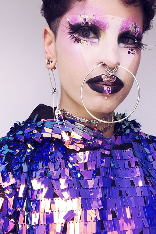 Juliana Delgado Lopera gazes into the camera dressed in purple rectangular sequins and with glitter and purple makeup around their eyes and a variety of hoops in their septum piercing