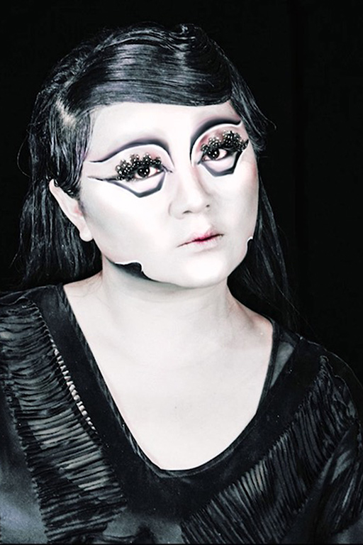 Du Yun is pictures against a black background with white makeup and black polkadot-ed feather eye lashes.They have stark black make-up highlighting their features and a splendid black feathered dress.