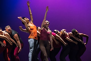 Students in the Mills College graduate Dance Department perform a piece, bodies and arms outstretched in various poses against a purple backdrop.