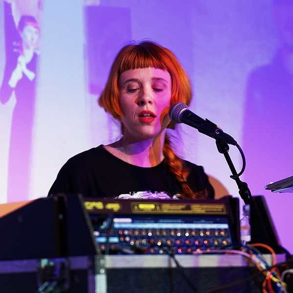 Electronic music composer, performing artist, and Mills alumna Holly Herndon sings into a microphone while seated behind a laptop and music mixer.