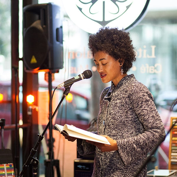 A young woman reads into a mic from an open book.