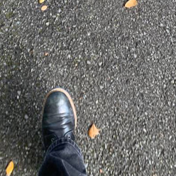 A right foot, in a black leather show steps forward over a blacktop sidewalk, blurred by the speed of walking. Photo by Steed Cowart.
