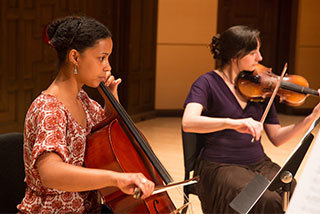 Two Mills College undergraduate music students play a cello and violin duet.