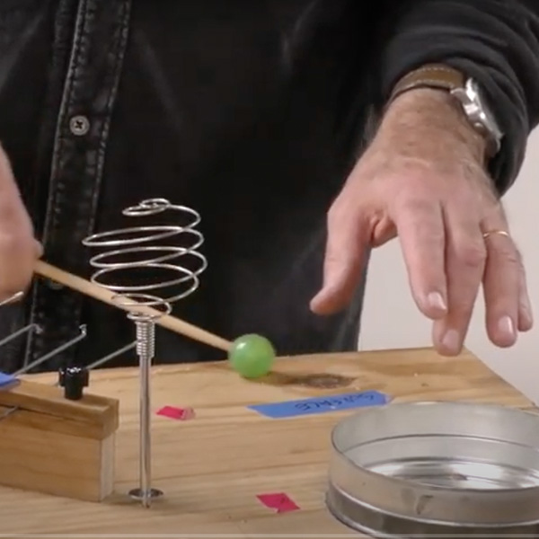 An array of objects sit on a wooden board: a upside down spiral whisk, a portion of a coffee caen. A green rubber mallet is striking the board near some blue and pink tape. a left hand floats sensitively over the board. Photo still from video.