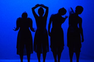 Students in the Mills College undergraduate Dance Department perform a piece, their shapes silhouetted against a blue backdrop.