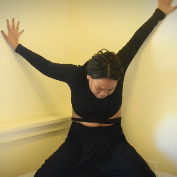 Dancer Vu Mbambo stands in a corner, dressed in black with her hair pulled back in braids, with both arms stretched up between the walls and her head down